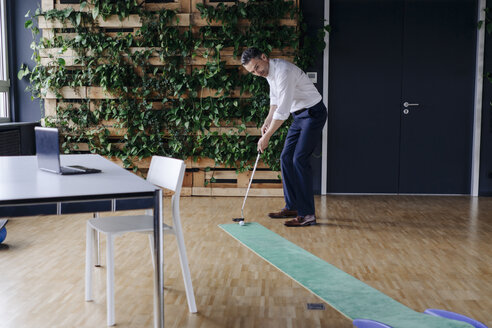 Businessman playing golf in green office - JOSF01410