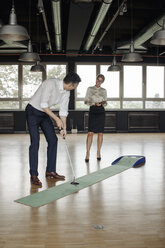 Businessman playing golf in office - JOSF01413