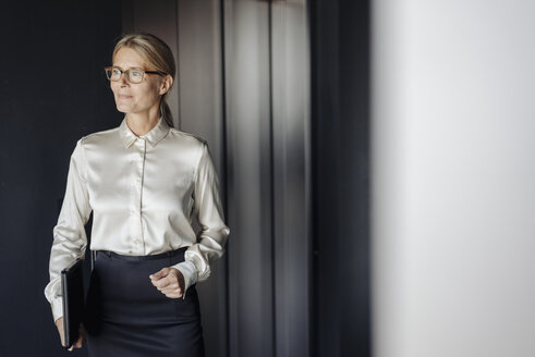 Confident businesswoman in office holding laptop - JOSF01428