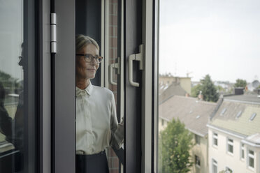 Businesswoman in office looking out of window - JOSF01431