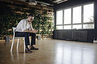 Businessman sitting on chair in green office looking at cell phone - JOSF01437