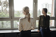 Two businesswomen in office looking out of window - JOSF01446