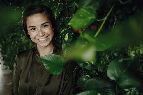Portait of smiling young woman at wall with climbing plants - JOSF01449