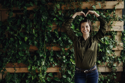 Portait of smiling young woman shaping heart at wall with climbing plants - JOSF01452
