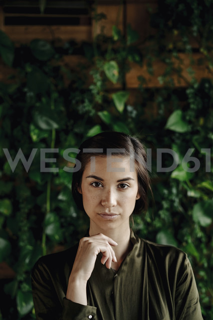 Portait of young woman at wall with climbing plants - JOSF01455