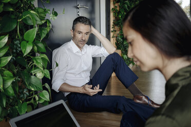 Businessman and businesswoman sitting on the floor in green office using tablet - JOSF01461