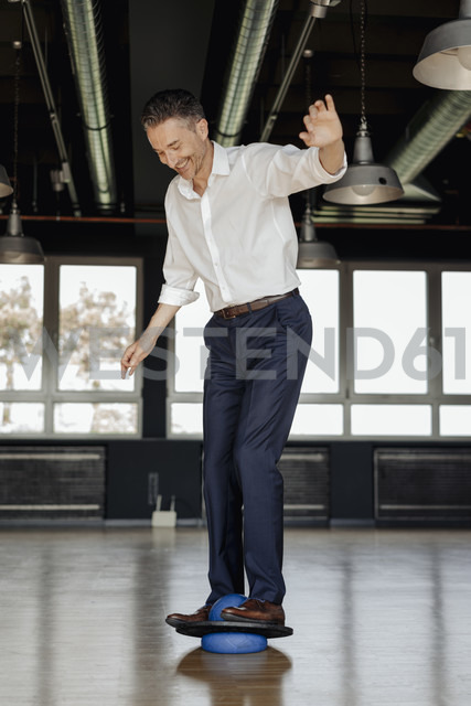 Businessman balancing on ball in office - JOSF01476