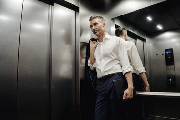 Businessman in elevator holding laptop - JOSF01479
