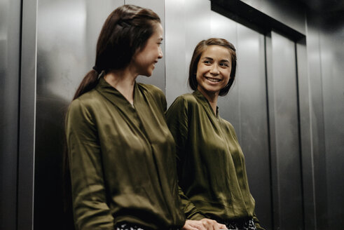 Smiling young woman looking in mirror in elevator - JOSF01485