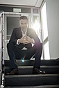 Portrait of confident businessman sitting on stairs - JOSF01497