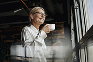 Smiling businesswomanholding cup of coffee looking out of window - JOSF01503