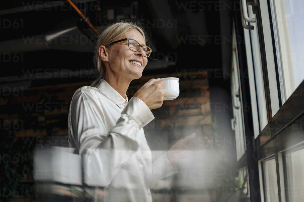 Smiling businesswomanholding cup of coffee looking out of window - JOSF01503 - Joseffson/Westend61