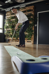 Businessman playing golf in office - JOSF01512