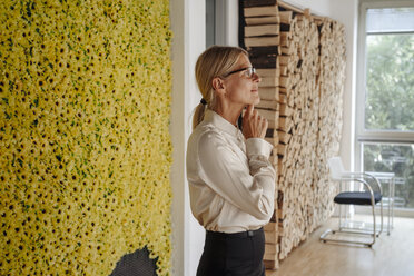 Businesswoman in office at wall with sunflowers thinking - JOSF01521