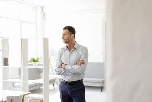 Businessman in office looking sideways - KNSF02416