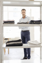 Portrait of confident businessman standing at shelf with clothes - KNSF02422