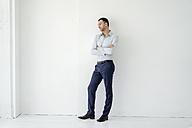 Businessman standing looking sideways - KNSF02425