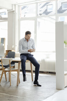 Businessman in office looking at cell phone - KNSF02428