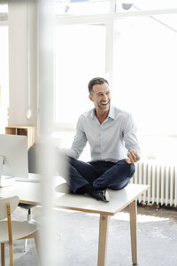 Happy businessman sitting on table in office practising yoga - KNSF02437