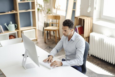 Businessman using computer at desk in office - KNSF02440