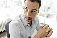Portrait of businessman in office looking back - KNSF02443