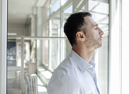Businessman with closed eyes at the window - KNSF02446