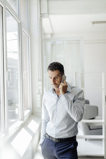 Businessman at the window in office on cell phone - KNSF02449