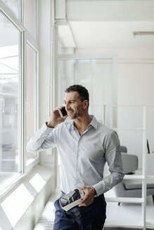 Businessman on cell phone at the window holding VR glasses - KNSF02455