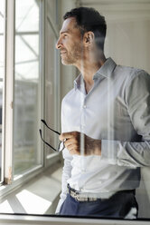 Businessman holding glasses looking out of window - KNSF02458