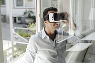 Businessman at the window wearing VR glasses - KNSF02461