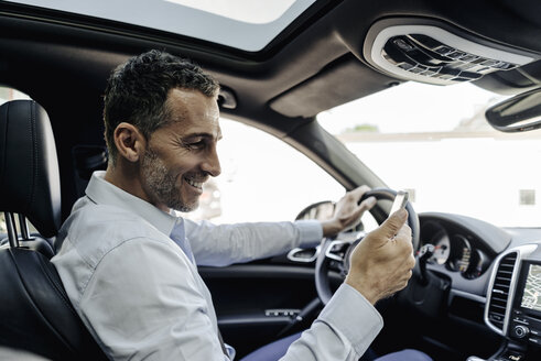 Businessman driving car looking at cell phone - KNSF02470