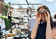 UK, London, Portobello Road, portrait of laughing woman looking through old binoculars - MGOF03582