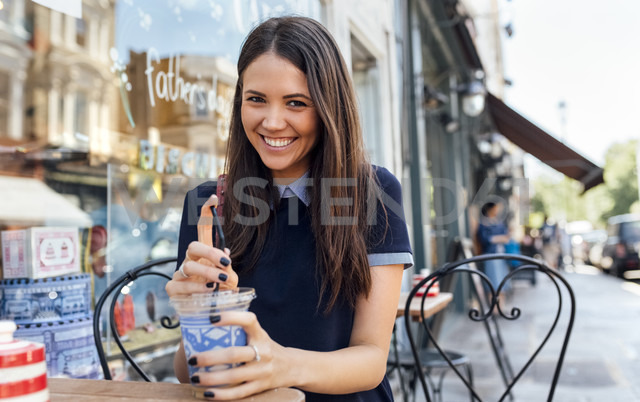 UK, London, Nottinghill, portrait of happy young woman with beverage at pavement cafe - MGOF03594