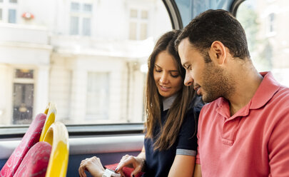 UK, London, couple sitting in a double decker bus using smartwatch - MGOF03597