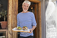 Mature man standing in front of his restaurant, serving a dish - WESTF23487