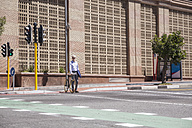 Mature man waiting at crossing with his bicycle - WESTF23544