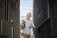 Mature man with longboard in an alley - WESTF23562