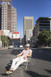 Mature man sitting on chair in the street, wearing sunglasses - WESTF23571