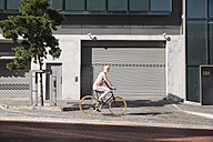 Mature man riding bicycle in the city - WESTF23574