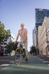Mature man riding bicycle in the city - WESTF23577