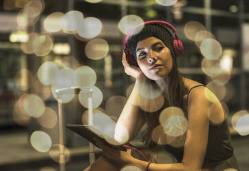Portrait of young woman with headphones and tablet waiting at station by night - UUF11622