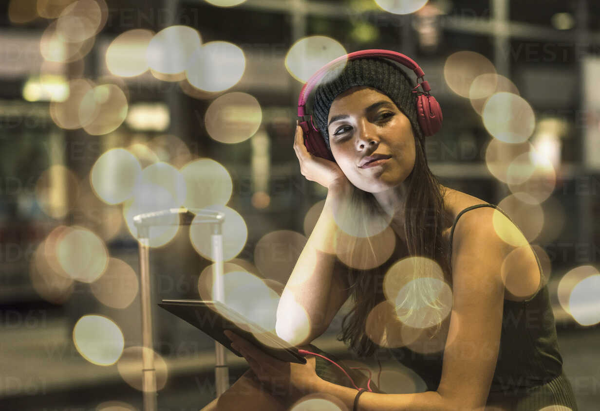 Portrait of young woman with headphones and tablet waiting at station by night - UUF11622 - Uwe Umstätter/Westend61