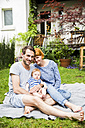 Family portrait of happy couple with baby boy sitting on blanket in the garden - SPFF00005