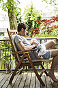 Mature man sitting on balcony with baby boy - SPFF00014