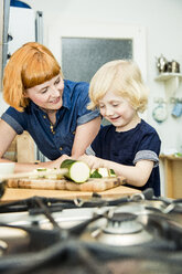 Littel boy chopping vegetables in the kitchen while his mother watching him - SPFF00017