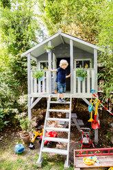 Portrait of little boy standing on ladder of frame house in the garden - SPFF00026