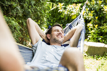 Portrait of laughing mature man lying in hammock in the garden - SPFF00047
