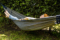Woman relaxing in hammock in the garden - SPFF00050