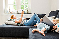 Mother and little son relaxing together on the couch with cell phone and tablet - SPFF00059