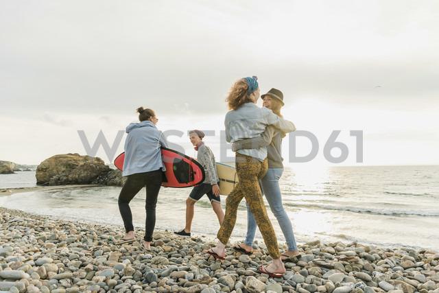 Happy friends with surfboards walking on stony beach - UUF11641